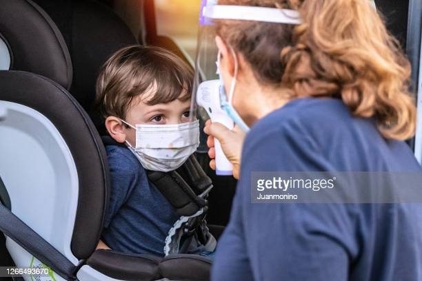 school employee taking temperature to a little child boy before he goes back to school - bubonic plague stock pictures, royalty-free photos & images
