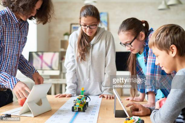 school friends holding experiment with toy vehicle - stem stock photos and pictures