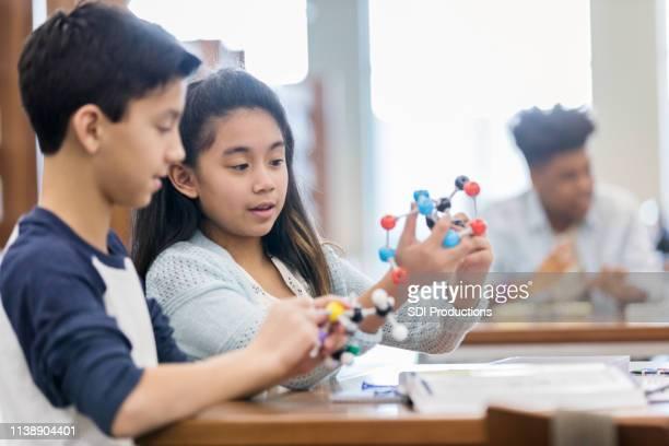 los amigos escolares trabajan en la asignación de ciencias - átomo fotografías e imágenes de stock