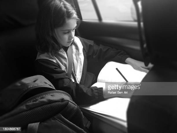 school girl doing homework in car - rafael ben ari photos et images de collection
