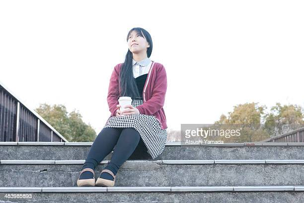 School girl having coffee and sitting on stairs