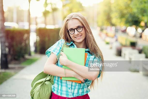 School girl holding textbooks on the street