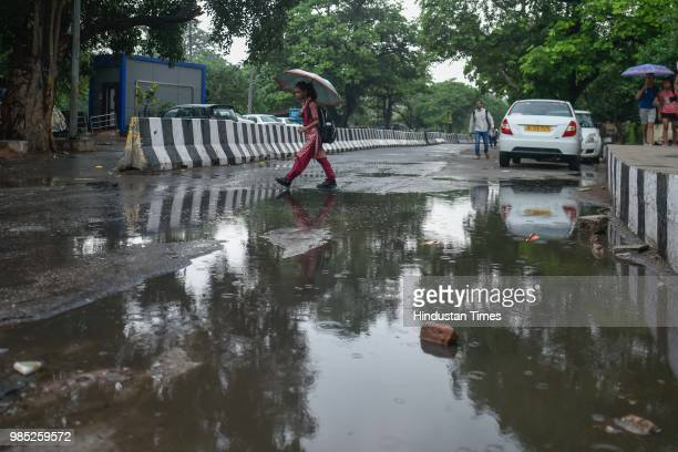 A school girl holds umbrella as she walks through a water logged road after the Capital witnessed a spell of premonsoon showers near Sheikh Sarai on...