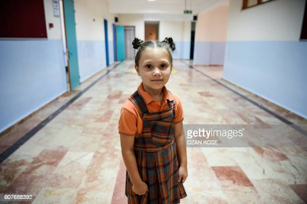 TOPSHOT A school girl in her uniform stands in the corridor during the first day back at school on September 19 2016 in Istanbul Turkish children...