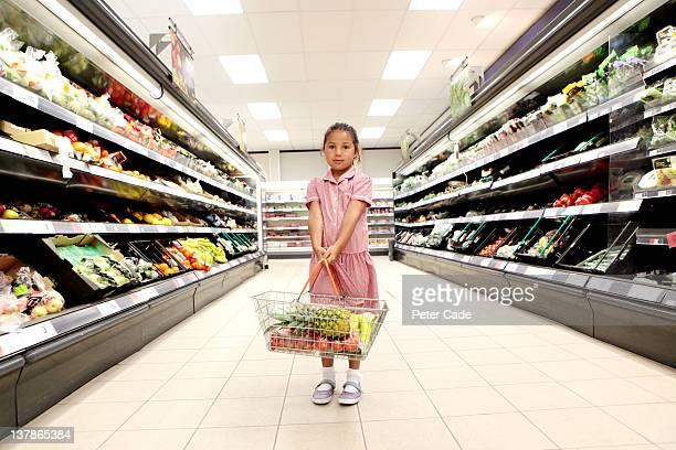 school girl in supermarket holding basket