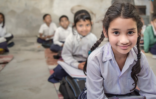 School girl in uniform of Indian Ethnicity sitting in their village classroom, looking at camera smiling. 896366108
