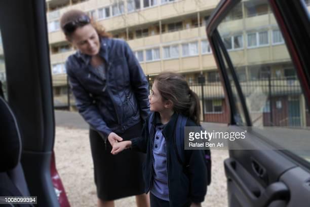 school girl looks at her mother on the way to home/school - rafael ben ari stock-fotos und bilder