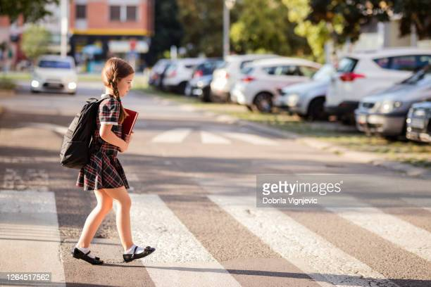 school girl on pedestrian crossing - crossing stock pictures, royalty-free photos & images