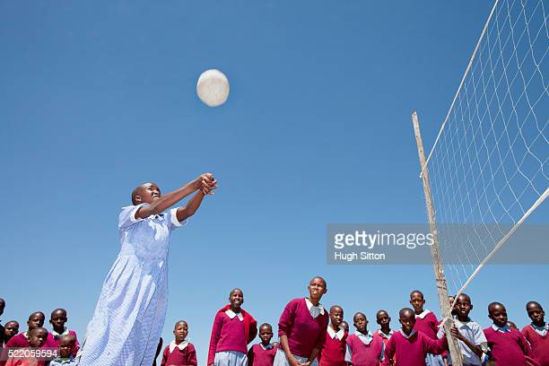 school girl (10-12) playing volley ball, other students watching - hugh sitton stock pictures, royalty-free photos & images
