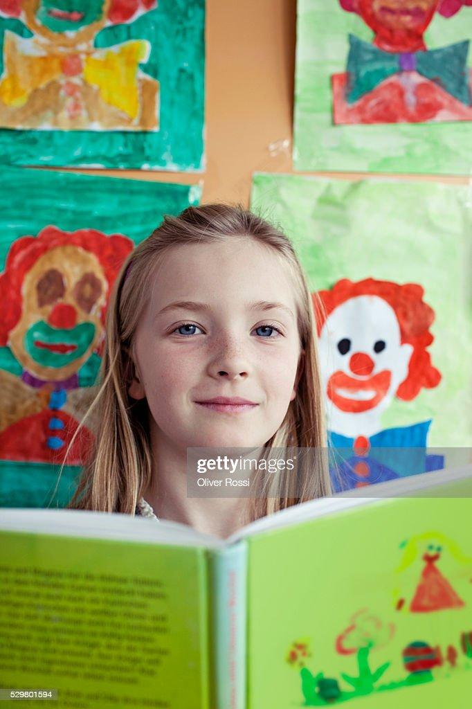 School girl (8-9) posing with book : Stockfoto