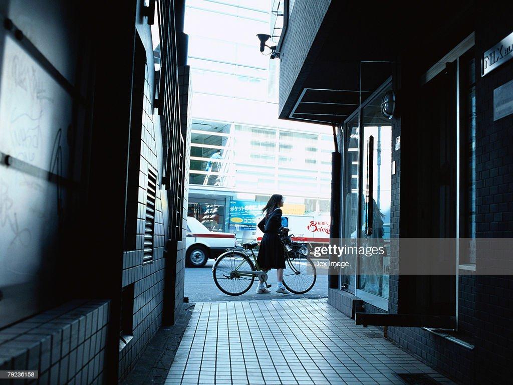 School girl pushing a bicycle : Stock Photo