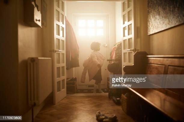 a school girl putting on her coat in the morning. - jacket stock pictures, royalty-free photos & images