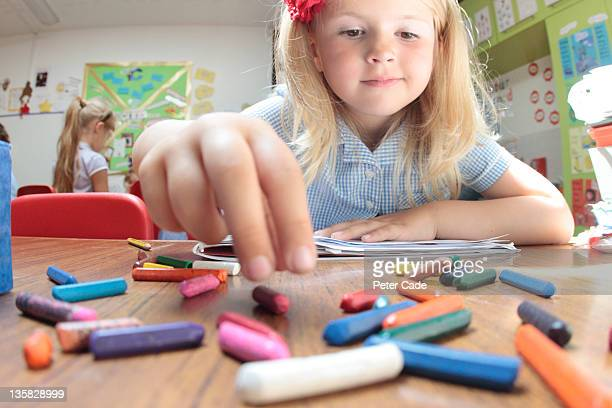 school girl reaching for coloured crayons