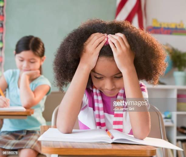 school girl reading book in classroom - 6 7 jaar stockfoto's en -beelden