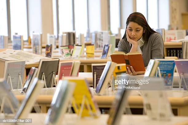 School girl (16-17) reading book in library