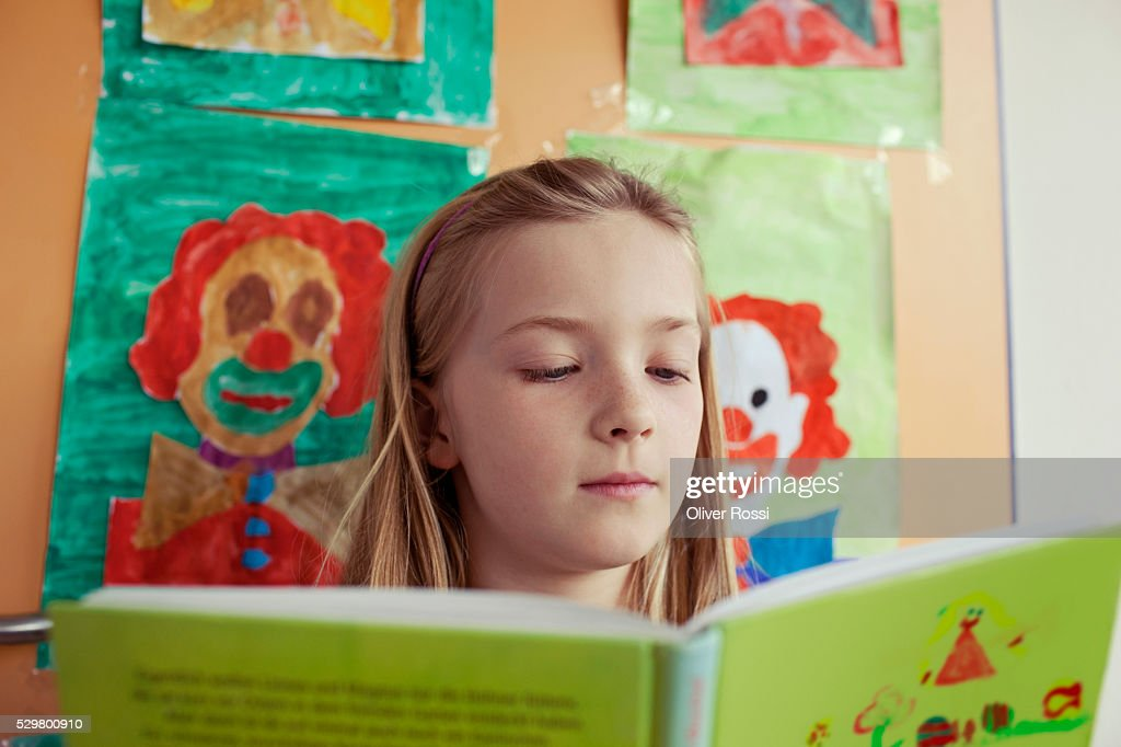 School girl (8-9) reading book : Stock Photo
