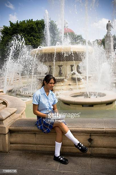 school girl sitting in center plaza by fountain - patio de colegio - fotografias e filmes do acervo
