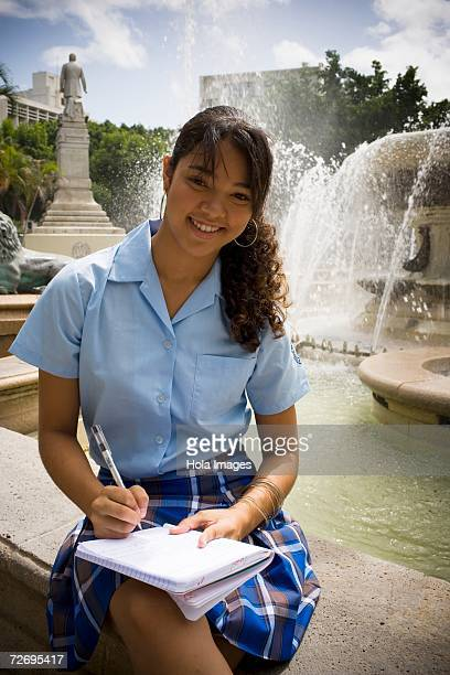school girl sitting in center plaza by fountain - patio de colegio imagens e fotografias de stock