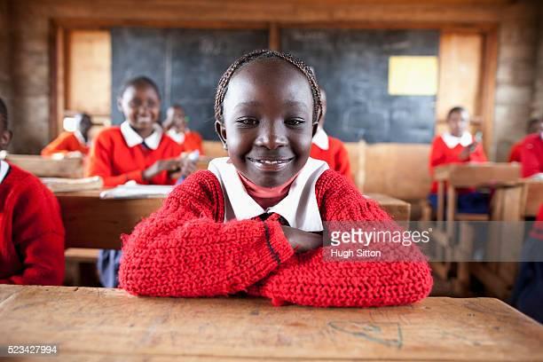 school girl sitting in classroom, kenya - hugh sitton stockfoto's en -beelden