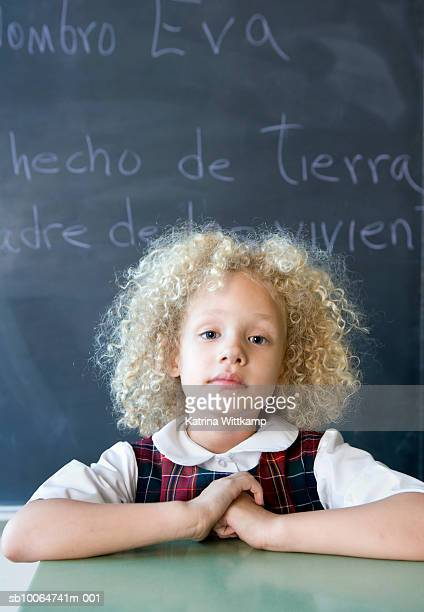 School girl (6-7) sitting in front of blackboard, portrait
