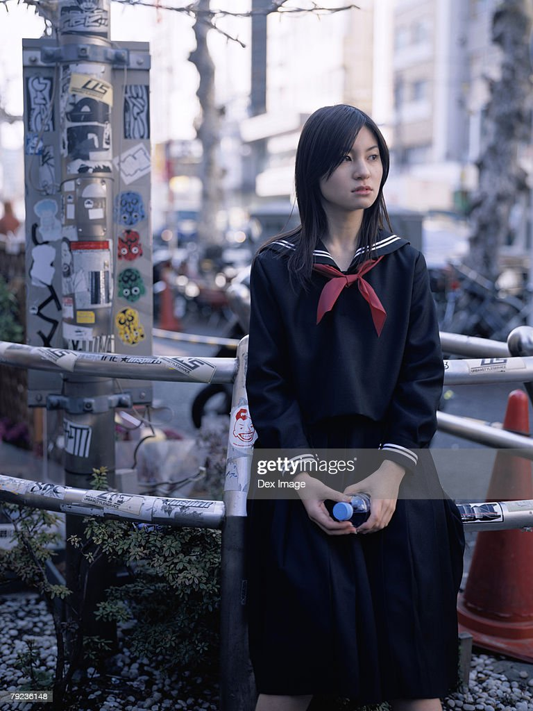 School girl sitting on a metal railing : Stock Photo