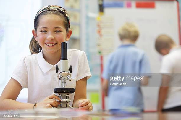 school girl smiling with microscope - ponytail stock pictures, royalty-free photos & images