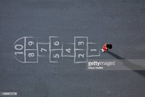 school girl standing in front big hopscotch - hopscotch stock pictures, royalty-free photos & images