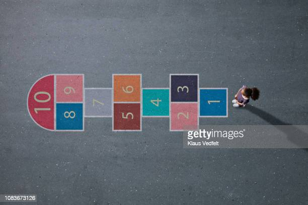 school girl standing in front big hopscotch - leisure games stock pictures, royalty-free photos & images