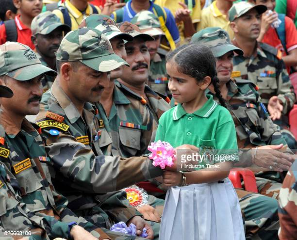 A school girl ties 'Rakhi' on the wrist of army soldier during the Raksha Bandhan festival celebrations at a school in Kathua about 85 KM on August 5...