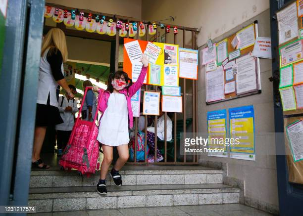 School girl waves as she gets inside the building to attend class at the Provincia de Cordoba school on February 17, 2021 in Buenos Aires, Argentina....