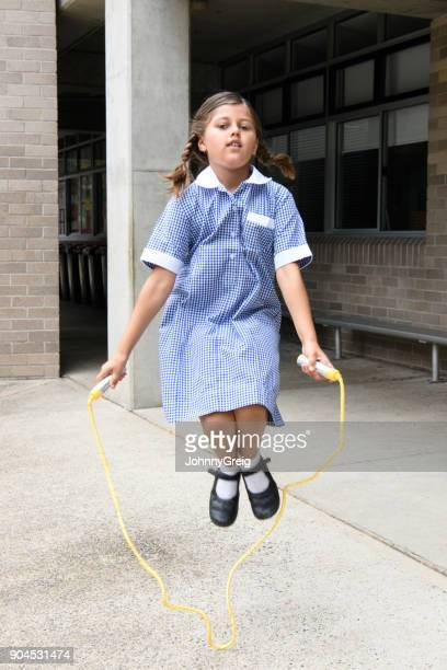 school girl wearing school dress using skipping rope in playground - skipping along stock pictures, royalty-free photos & images