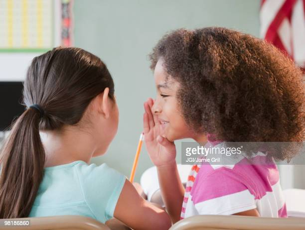 School girl whispering to friend