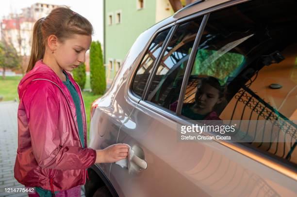 school girl wiping down car door handle before going to school - cristian neri foto e immagini stock