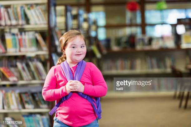 School girl with down syndrome in library