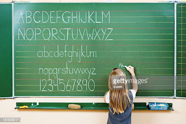 School Girl Writing On Blackboard, Rear View