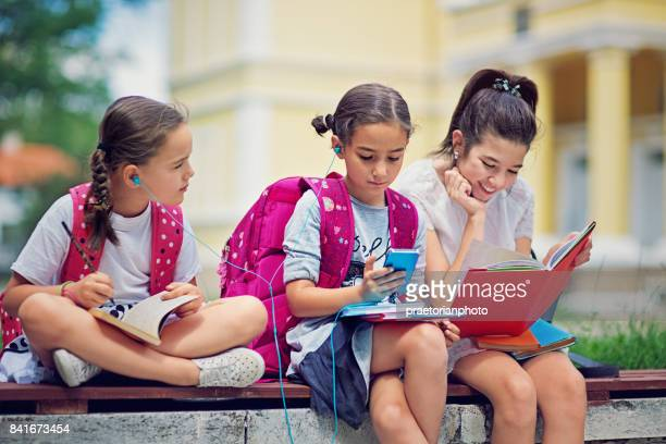 School girls are taking a break from lessons and sitting in the school yard
