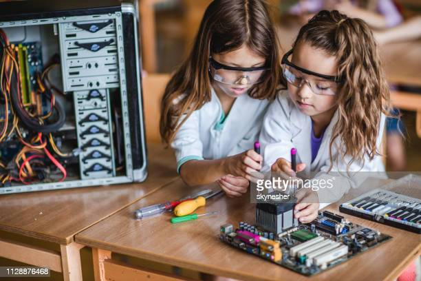 school girls cooperating while repairing mother board in the classroom. - stem stock photos and pictures