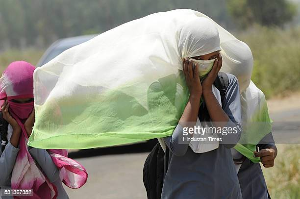 School girls cover their faces to protect themselves from the scorching sun as they walk home after school on a hot and humid day on May 14 2016 in...
