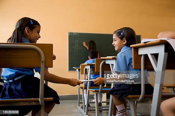 School girls exchanging a notebook