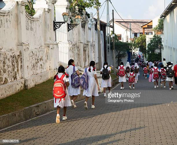 School girls in uniform walking in a street in the historic town of Galle Sri Lanka Asia
