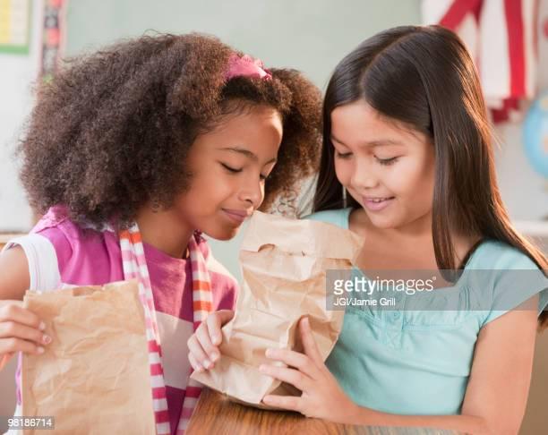School girls looking into lunch bag