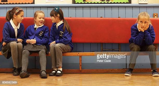 School girls on bench, one excluded