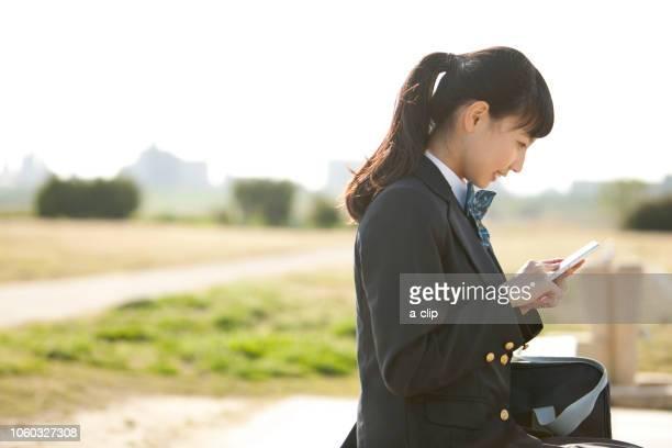 スマートフォンを操作する女子校生 - 制服 ストックフォトと画像