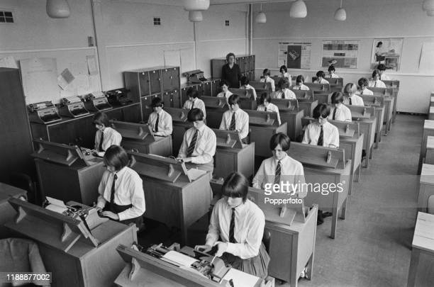 School girls sit at desks to operate typewriters during a typlng skills and secretarial class in a secondary school in Birmingham England in July 1966