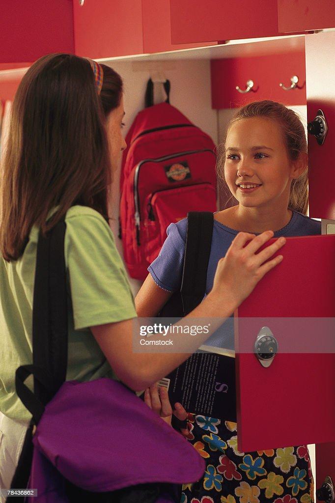 School girls socializing at their lockers : Stockfoto