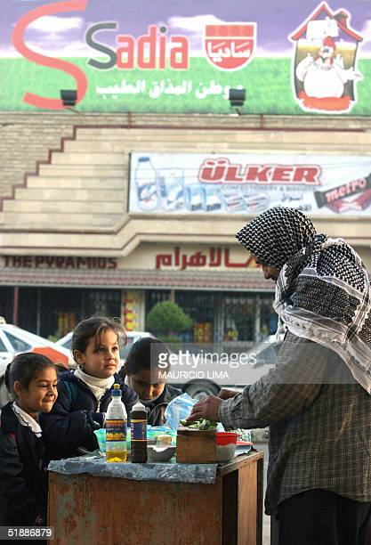 School girls stop to buy egg sandwiches from a street vendor close to the main entrance of the French Embassy in Baghdad 22 Devcember 2004, where...