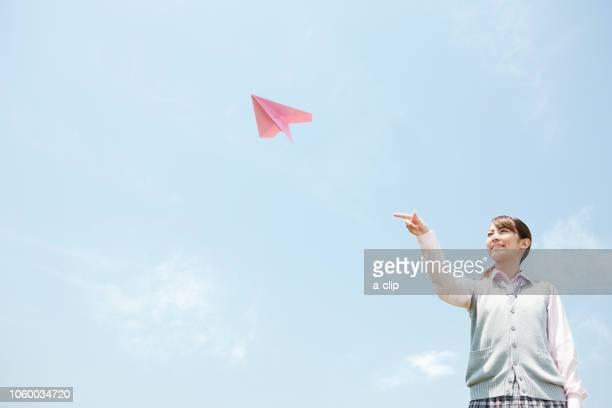 紙飛行機を投げる女子校生 - 投げる ストックフォトと画像