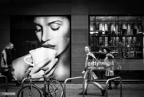 School girls walk past a poster of lady drinking coffee, Adelaide, Australia.