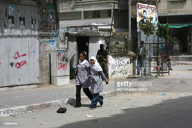 School girls walks past armed Palestinian militants from the alAqsa Martyr's Brigades as they stand on the streets of Beit Lahiya in the northern...