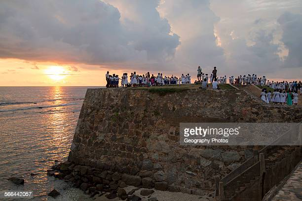 School group on fort ramparts at sunset in historic town of Galle Sri Lanka Asia